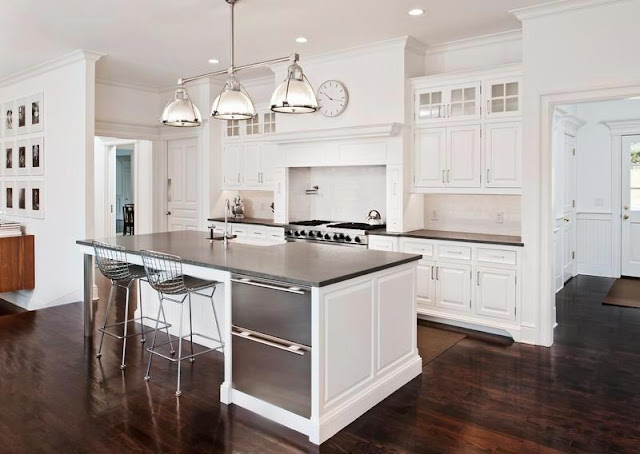 white kitchen in a mansion with dark wood floors, an island, wire chairs, stainless appliances and a pendant style chandelier
