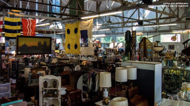 Antique store with lamps, flags, and paintings