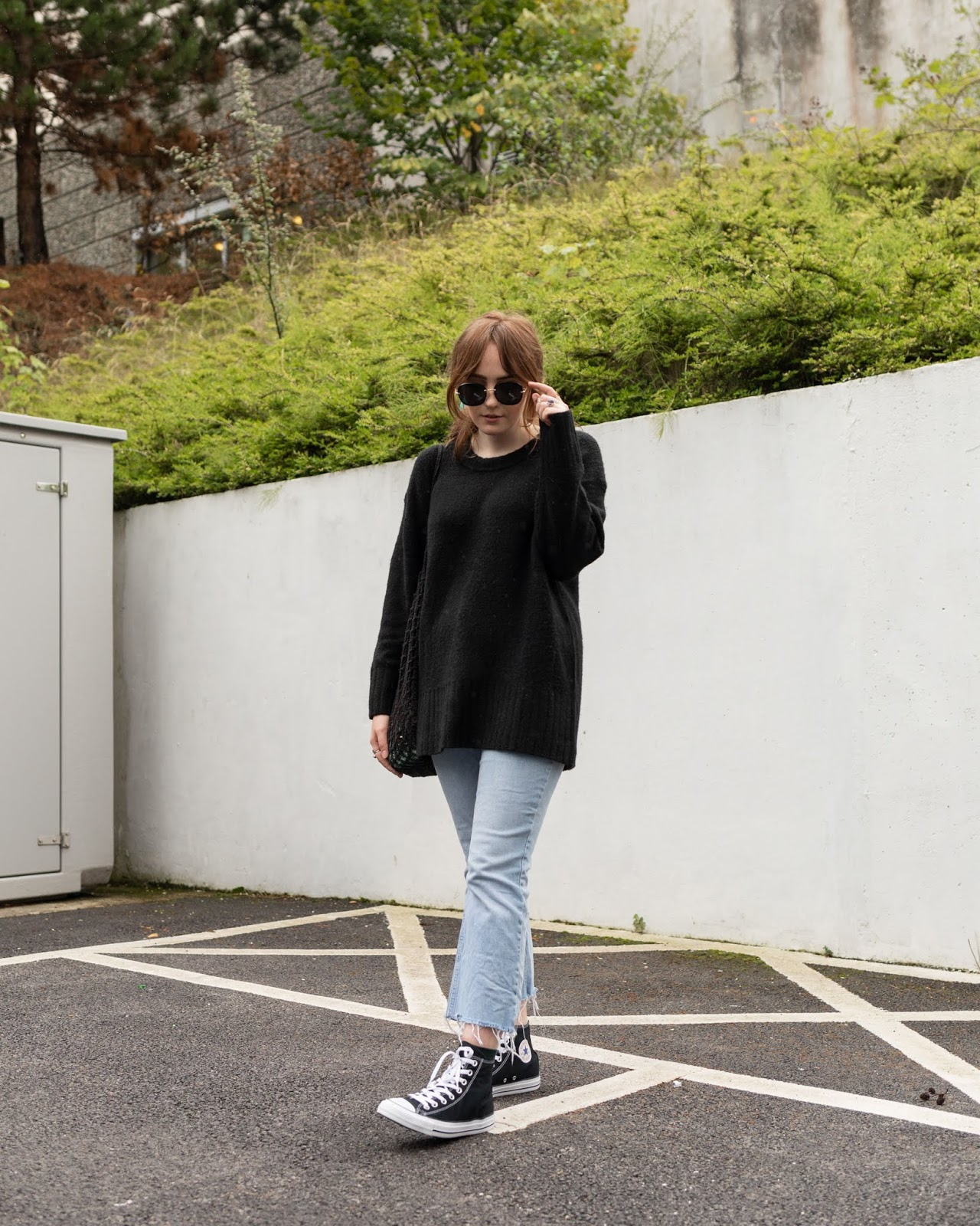 uk fashion blogger wearing oversized black jumper and light wash kick flare crop jeans and black converse with green scarf in ponytail