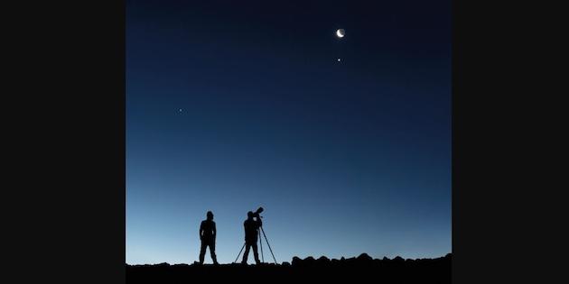 Dos siluetas observando en cielo con telescopio personal. Crédito ESO