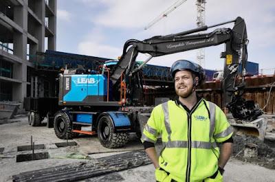 Linus Josefsson på arbetsplats i arbetskläder med sin grävmaskin bakom sig.