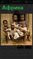Дети с черным цветом лица в Африке держат на руках маленьких щенков около входа в дом