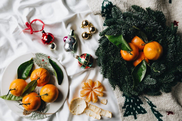 Festive table of oranges, Christmas baubles and holly wreath