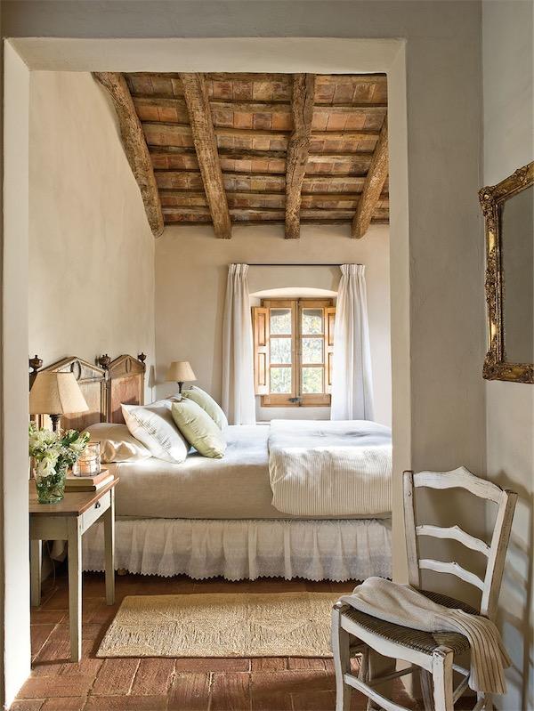 dormitorio rustico con techo de madera y vigas vistas