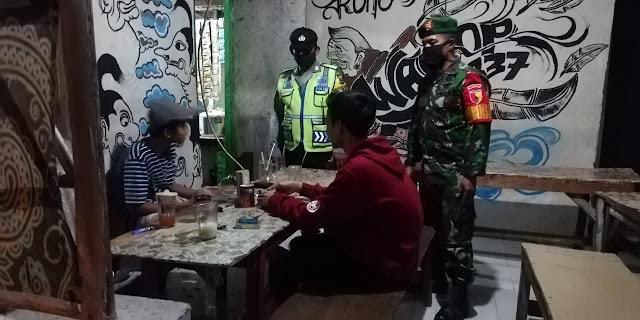 """Mojokerto, - Personel Koramil 0815/05 Gedeg Kodim 0815/Mojokerto bersama anggota Polsek Gedeg menggelar patroli di sejumlah warung kopi (Warkop) di Desa Gedeg Kecamatan Gedeg Kabupaten Mojokerto, Jawa Timur, Selasa (16/06/2020) malam.  Patroli gabungan ini dilakukan dalam rangka memonitoring situasi dan kondisi para pengunjung warung kopi sekaligus memperketat penerapan protokol kesehatan Covid-19.  Tak hanya monitoring, patroli gabungan ini juga memberikan himbauan dan arahan kepada pengunjung agar selalu melaksanakan protokol kesehatan dengan cara sering cuci tangan pakai sabun, mamakai hand sanitizer, memakai masker dan menjaga jarak aman di antara pengunjung.  Di tempat terpisah, Danramil 0815/05 Gedeg Kapten Infanteri Mulyono, saat dikonfirmasi, membenarkan adanya kegiatan patroli tersebut. Menurutnya patroli tersebut bertujuan untuk memutus rantai penyebaran Covid-19.   """"Dengan patroli di sejumlah warung kopi dan tempat keramaian lainnya, merupakan salah satu cara untuk memantau secara langsung apakah para pengunjung sudah menerapkan protokol kesehatan atau belum, seperti tertib cuci tangan dan mengenakan masker, jika masih ditemukan ada yang tidak mengenakan masker tentunya akan kami tegur,"""" ungkapnya.  Ditambahkan Babinsa Koramil 0815/05 Gedeg Pelda Rusmanto, tingkat kesadaran masyarakat sudah meningkat, terbukti saat melaksanakan patroli bersama di sebuah warung kopi, ternyata masyarakat sudah mengenakan masker, cuci tangan dan jaga jarak aman. (Jayak)"""