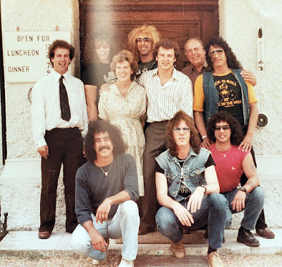 "Twisted Sister 1982 UK London... Great fucking photo!!! This is the boyz in front of the hotel where they were staying in during the recording of ""UNDER THE BLADE""... too fuckin' cool!! Standing... Mark, Dee, Eddie, with the 4 owners of the hotel. Kneeling... Charlie ""sixth Sister"" Barreca, Jay Jay, A.J. 19-fucking-82 muthafucka!! WOW!! Love it!"