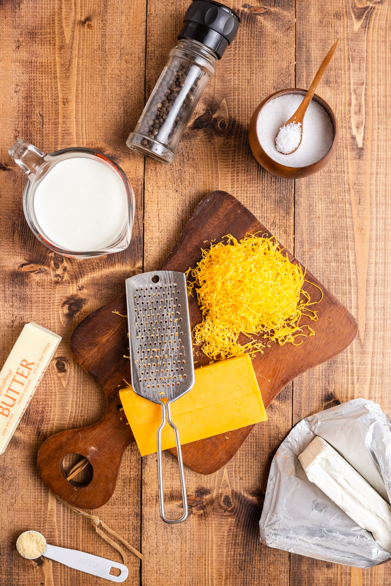 Over head photo of ingredients needed to make Easy Keto Cheese Sauce on a wooden table.