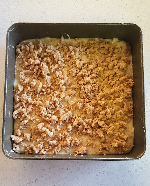Image Description: A downward facing image of a square cake pan with unbaked coffee bars and streusel.
