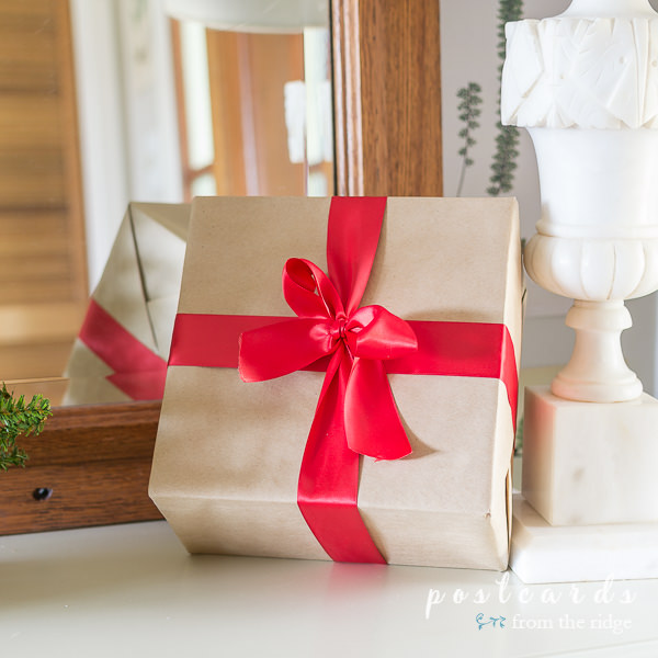 small package wrapped with kraft paper and tied with a red satin bow