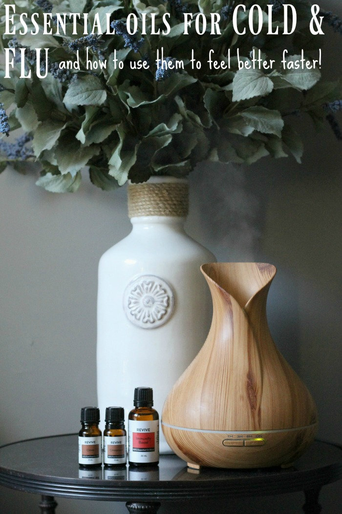 Essential oil bottles and diffuser with faux lavender in the background. Essential oils that assist with colds and flu