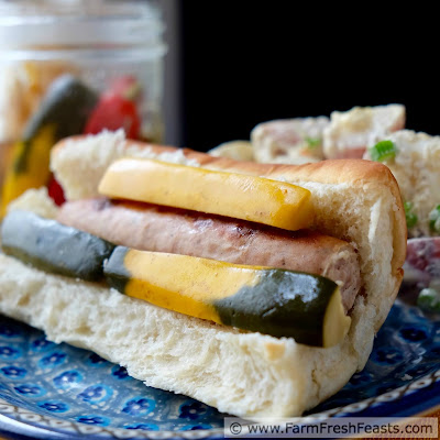 a photo of a bratwurst sandwich with hot and spicy zucchini pickles and potato salad