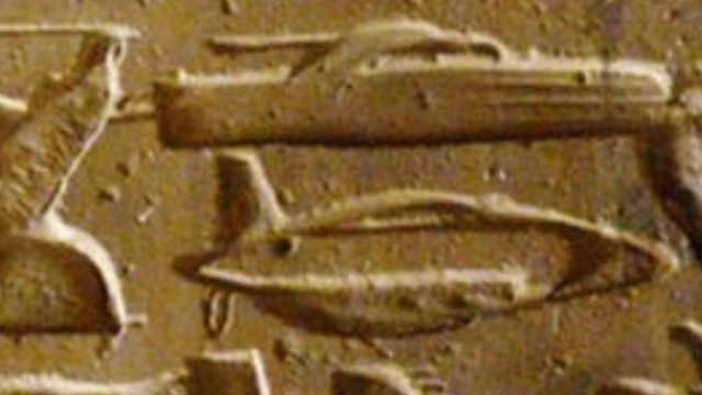 Close up of submarine and a tank from ancient Egyptian temple carving.
