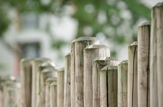 A fence composed of circular poles of varied heights.