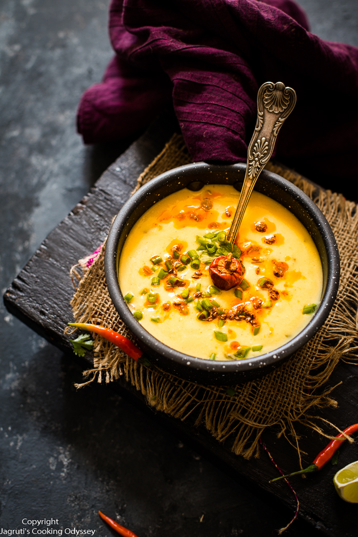 Spring onion kadhi is served in a pan, pan is placed on a black wooden blackboard.
