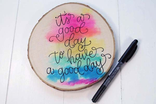Write callligraphy or bounce lettering on a watercolor washed woodslice