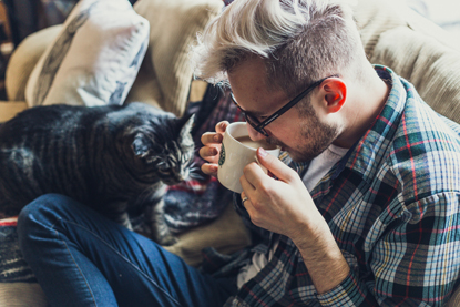 man drinking coffee on sofa with tabby cat next to him