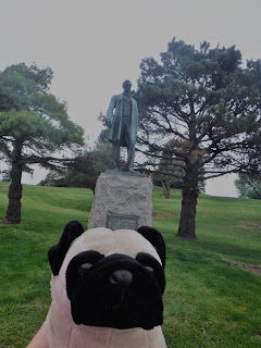 a weathered green statue of Abraham Lincoln stands atop a stone pedestal in a grassy park between two trees behind a plush pug.