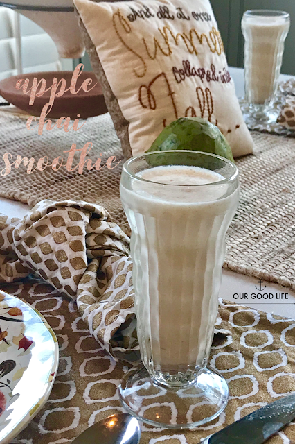 Crystal glass of apple chai smoothie, sitting on a gold and white placemat