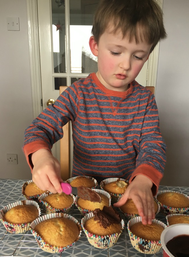 boy-spreading-chocolate-icing-on-cup-cakes-made-in-Disney-store-Mickey-Mouse-cup-cake-cases-