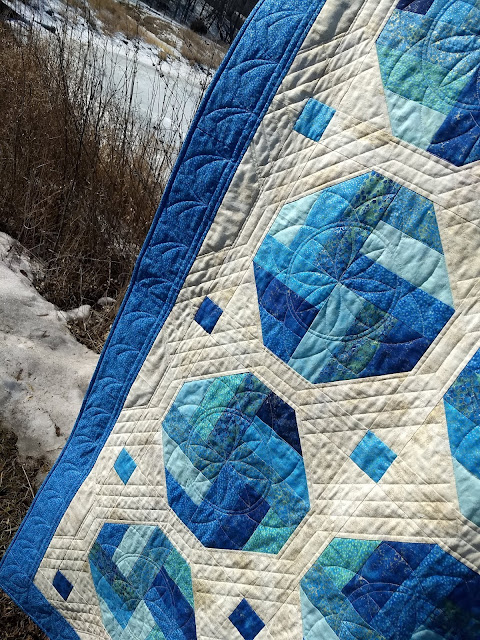 Quilt with blue border and octagons made of assorted blue precut strips, on a creamy gold background.