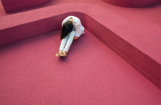 woman sitting looking sad on pink ground