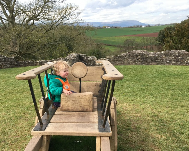 toddler sat in wooden cart with view behind