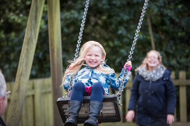 A child sitting on a swing in a playground for free with mum in background