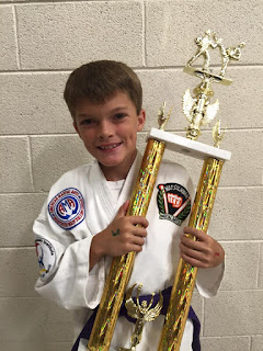 A karate kid holds a trophy he won doing the best martial arts for kids