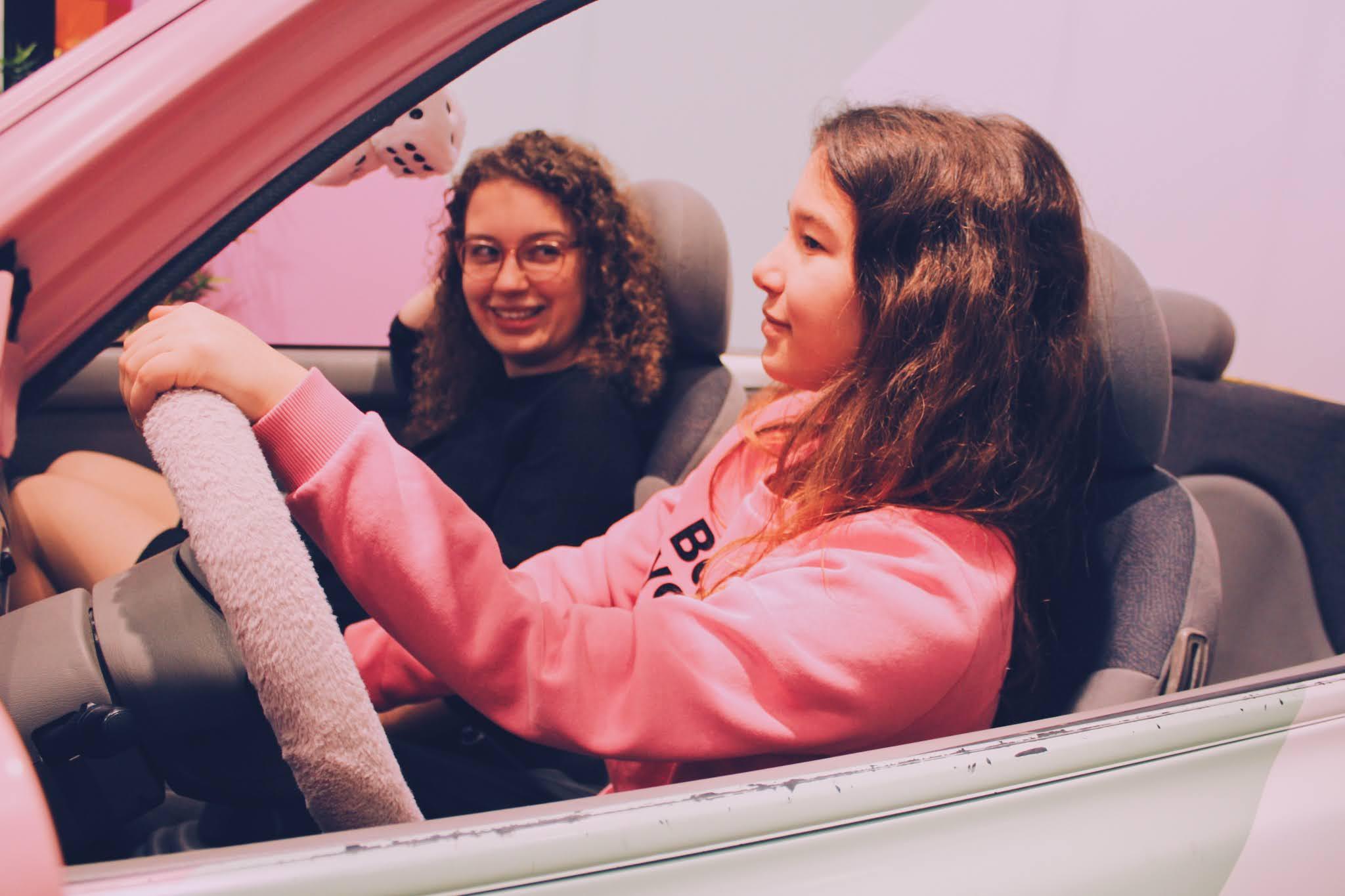 Mijn zus en ik zittend in een roze auto