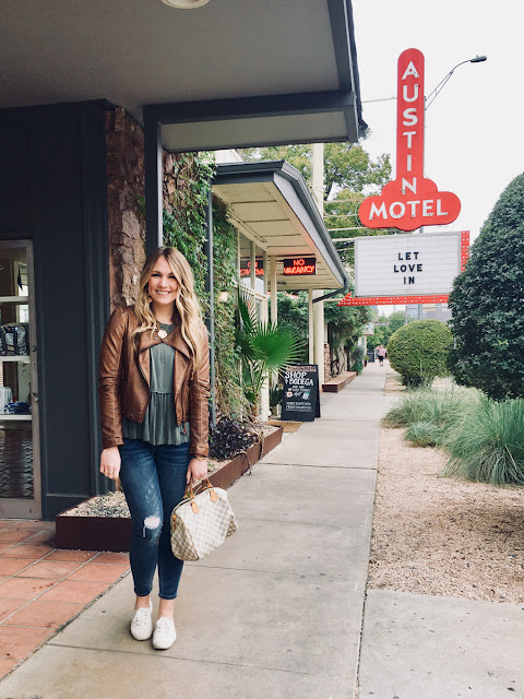 Tourist standing in front of Austin Motel sign