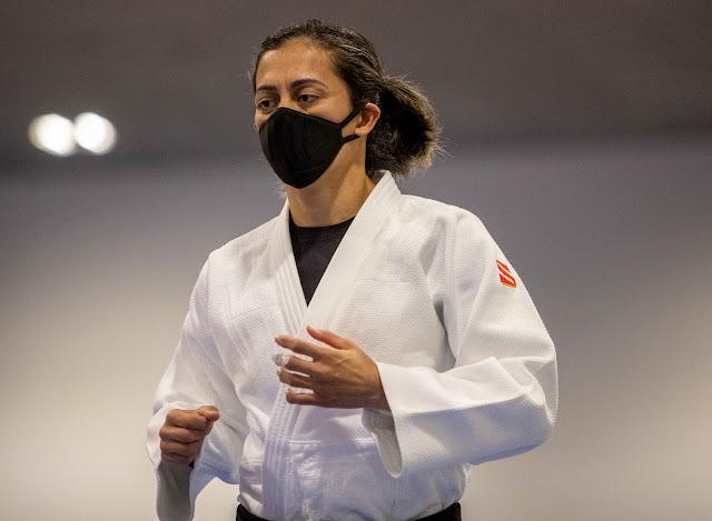 Lúcia Araújo usando um judogui branco e com uma máscara preta no rosto