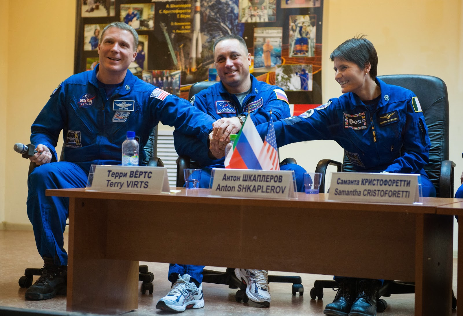 Expedition 42 Flight Engineer Terry Virts of NASA, left, Soyuz Commander Anton Shkaplerov of the Russian Federal Space Agency (Roscosmos), center, and Flight Engineer Samantha Cristoforetti of the European Space Agency (ESA), right, pose for a photo at the conclusion of the press conference, Saturday, Nov. 22, 2014, at the Cosmonaut Hotel in Baikonur, Kazakhstan. The mission to the International Space Station is set to launch Nov. 24 from the Baikonur Cosmodrome. Photo Credit: (NASA/Aubrey Gemignani)
