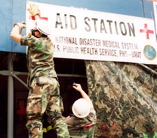 PHS officers hang up the AID STATION Banner at the damaged deli that was used as a makeshift clinic at Ground Zero. (Courtesy Photo)