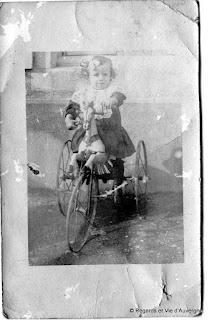 Photo de famille ancienne noir et blanc. enfant avec vieux cheval de bois sur roues