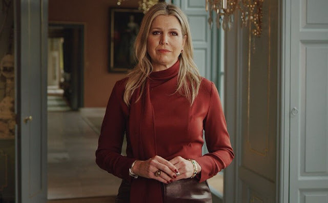Queen Maxima wore a burgundy stretch scarf collar silk crepe blouse from Natan. burgundy faux leather skirt