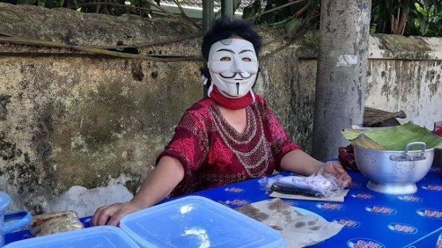 Iseng Berjualan Bubur Gunakan Topeng Anonymous, Dagangan Ibu ini Mendadak Viral dan Laris Manis