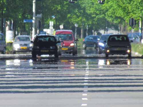 fenomena fatamorgana pada jalan raya beraspal terlihat genangan air di siang hari yang panas