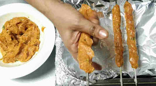 Placing mince chicken on a Shewer in cylindrical shape, two seekh kabab and mince Chicken on side