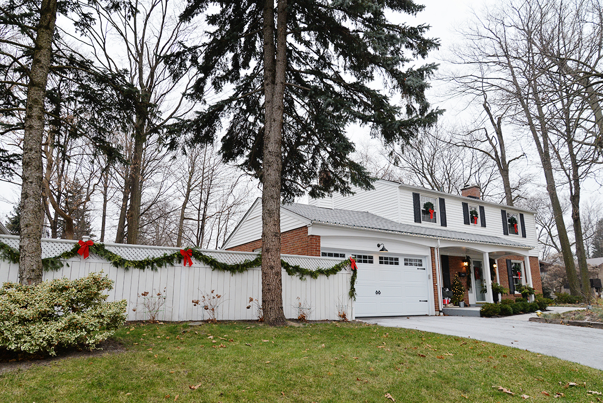 Christmas colonial house with garland on white fence