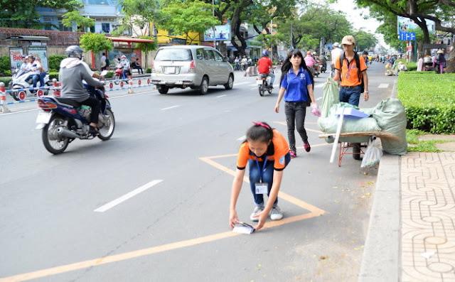 Các bạn trẻ tham gia nhặt rác, làm sạch đường phố trên đường Nguyễn Văn Cừ (TP.HCM) - Ảnh: HỮU KHOA. Báo Tuổi Trẻ.