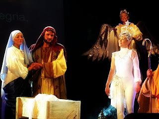 José e Maria, a Estrela Guia e o Anjo olham para o menino Jesus na manjedoura.