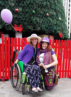 Jodie is on the left sitting in a green wheelchair. Ellen is kneeling next to her. They are both in front of a giant green christmas tree which is bordered by a red picket fence. There are decorated boxes ('presents') under the tree behind the fence.  Jodie is wearing a white hat with a purple bandana hat band and purple cardigan, black shirt and purple and black floral skirt and sandals.  Ellen is wearing a purple hat with a white hat band, a purple paisley scarf, a purple T shirt with a large white circle on the front of it. Inside the white circle is the purple word 'Dignity'. Ellen is wearing a medium length straight floral skirt and purple stockings.