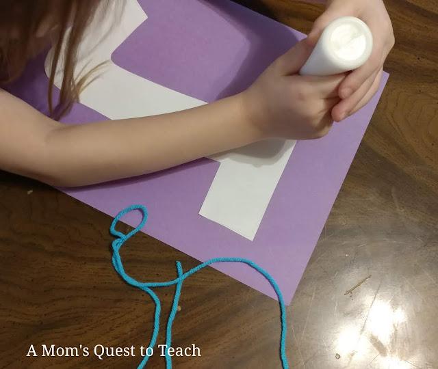 letter J made of construction paper glued onto purple construction paper; gluing yarn onto letter J