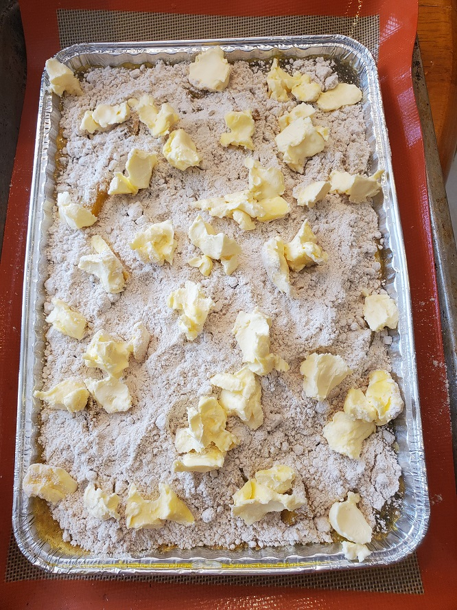 this is 3 ingredient dump cake with peaches and spice cake topped with sliced of butter