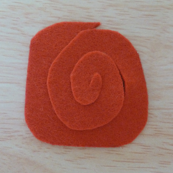 A spiral shape cut into the red felt circle