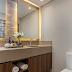 Banheiro bege e amadeirado com parede de pedras e espelhos retroiluminados!