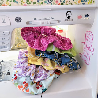 pile of fabric hair scrunchies stacked up on sewing machine throat space