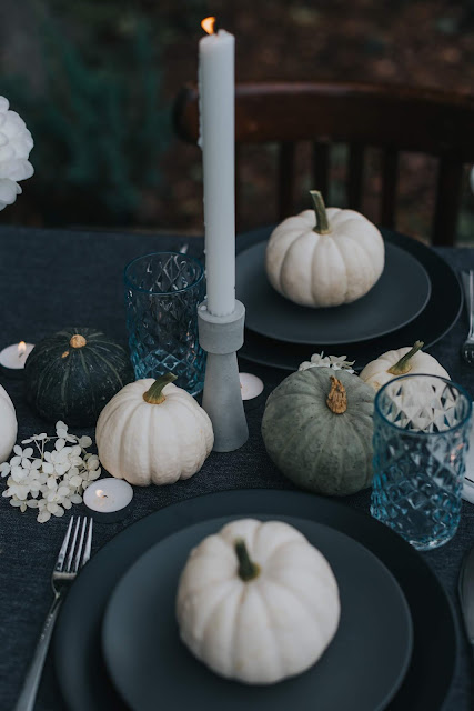 White pumkins on black table setting
