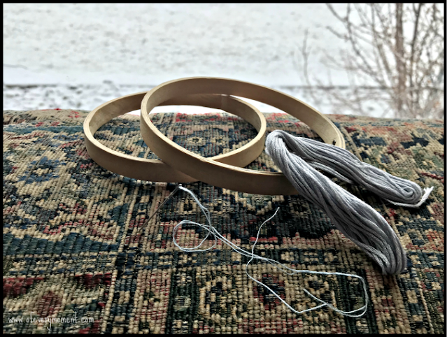 Embroidery hoops, thread and a needle resting on a tapestry in front of a window showing a snowy scene.