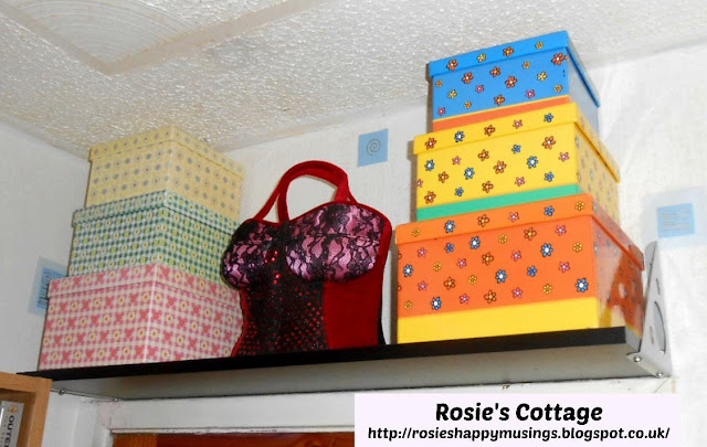 Shelf fitted above the closet door is used for pretty storage boxes which contain personal treasures and memories as well as a much loved handbag.